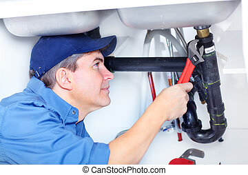Plumber - Handsome professional plumber doing sink...