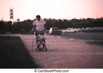 Little Boy In Stroller 1964 - A cute little boy waves to the...
