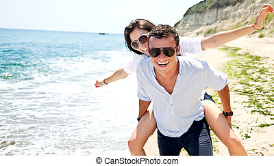 Young couple enjoing beach - Happy young couple with...