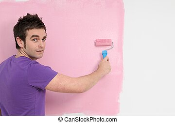 young man painting decorating with roller brush