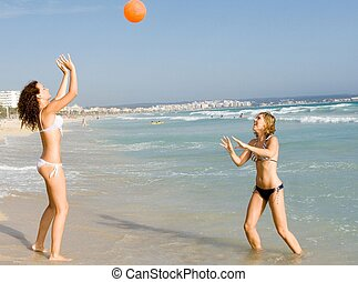 happy teens playing ball on beach summer vacation