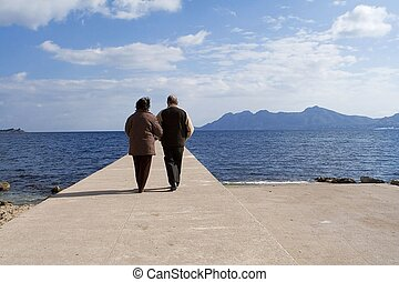 active senior couple walking by the sea on vacation