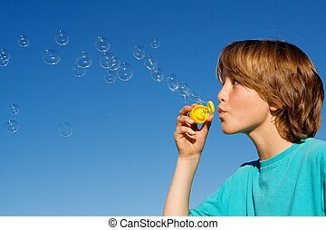 happy kid blowing bubbles with bubble wand