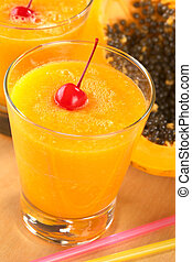 Fresh blended papaya juice garnished with a maraschino...