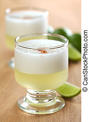 Peruvian cocktail called Pisco Sour made of Pisco (Peruvian grape schnaps), lime juice, syrup and egg white (Selective Focus, Focus on the front glass rim)