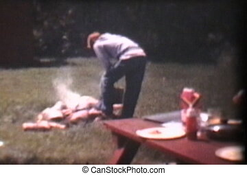 Putting Out Campfire 1975 Vintage - A young teenager takes...