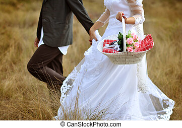 Bride and groom running on grassland