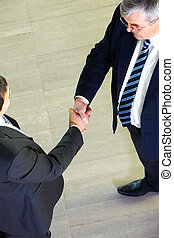Collaboration - Above view of two managers shaking hands