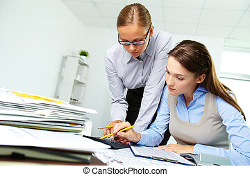 Office work - Portrait of two businesswomen working with...