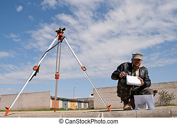 Theodolite on a tripod with construction worker - Surveyor...
