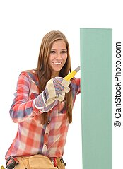 Woman cutting a green gypsum board - Young attractive woman...