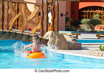 Boy playing in hotel pool - Young boy playing in outdoor...