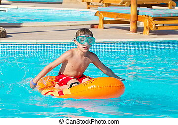 Boy playing in swimming pool - Cute young boy playing on...