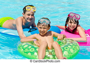 Children playing in pool - Happy young boys playing with...