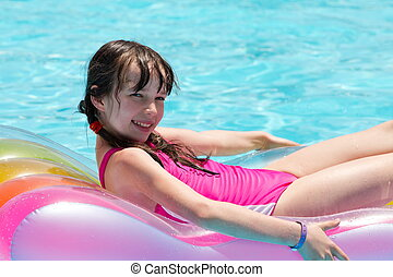 Girl relaxing on lilo in pool - Cute young girl relaxing on...