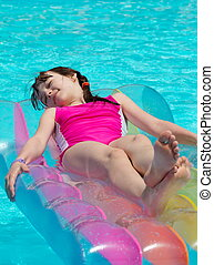 Girl on lilo in swimming pool - Cute young girl relaxing on...
