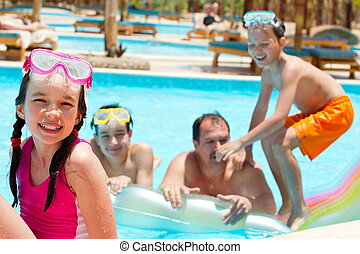 Happy family in swimming pool - Happy family of three...