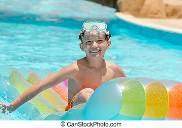 Happy boy on lilo in pool - Happy young boy playing on lilo...