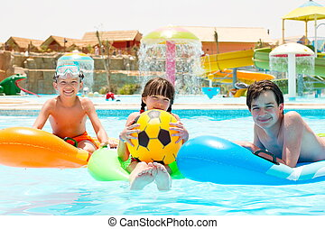 Children floating on pool toys