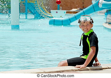 Happy boy in water park - Portrait of happy boy sat on edge...