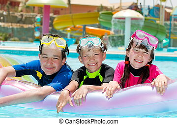 Kids in swimming pool - Three happy kids swimming in a pool....