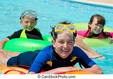 Kids playing in swimming pool - Three happy, smiling...