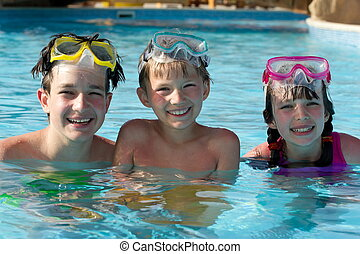 Happy children in pool - Happy young boys and girl in...