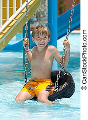 Boy on tire swing in pool - Happy young boy on tire or tyre...