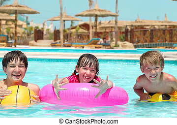 Happy children playing in pool - Happy young brothers and...