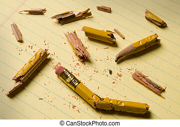 Broken pencil fragments on yellow paper - Shattered pencil...