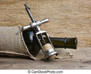 Old corkscrew and bottle of wine