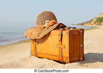 Yellow beautiful suitcase on a sea-shore