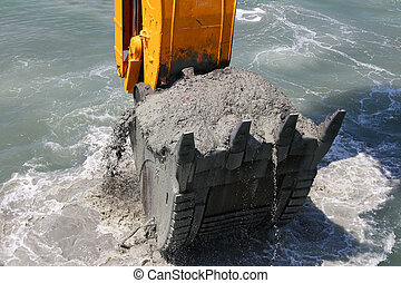 Excavator bucket of water from the soil of the seabed