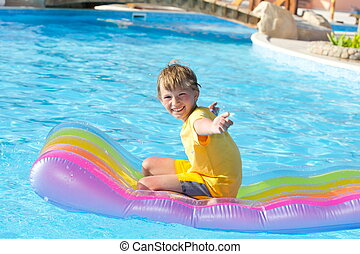 Happy boy playing in pool