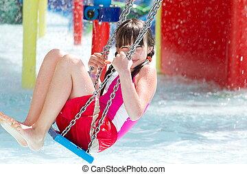Girl on swing in pool