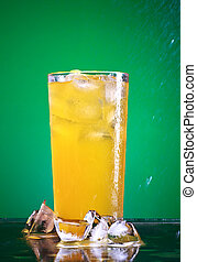 Soda Glass - glass of orange soda with ice over green...