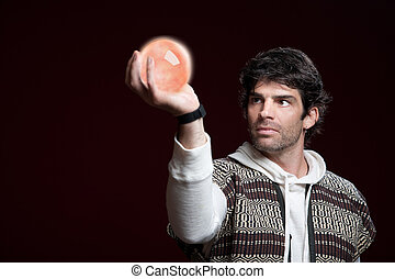 Man Holds a Crystal Ball - Caucasian man holds up a crystal...