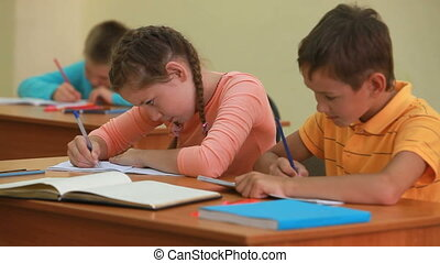 Schoolwork - Three little children writing tests in school