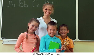 Portrait in classroom - Three pupils and their teacher...