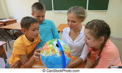 Geography lesson - Three pupils spinning a globe with their...