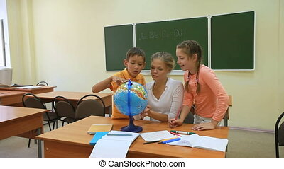 Learning the world - Two pupils and their teacher looking at...