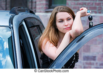 Young woman with a car key - Young woman with key near the...