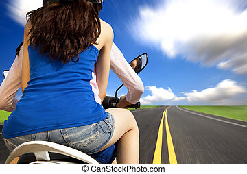 girls riding a motorcycle with high speed on a country road