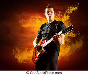 Rock guitarist play on the electric guitar around fire...