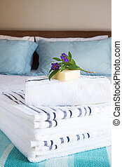 Beautiful bedroom interior with white sheets and striped...