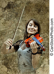 Beautiful female violinist playing violin on the grunge...
