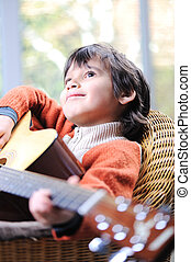 Portrait of young boy playing acoustic guitar at home
