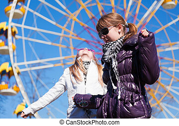 Teenage girls against a ferris wheel