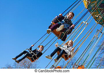 Teenage girls on the chain swing carousel
