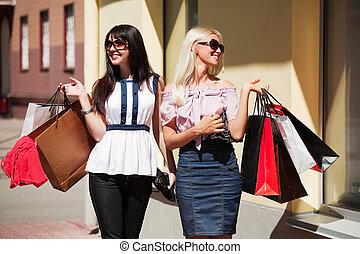 Two young women shopping - Two young women with shopping...